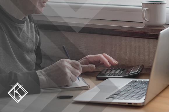 """Homem utilizando calculadora e notebook. A imagem ilustra a publicação """"Valor da pensão por morte servidor público federal: como calcular?"""""""