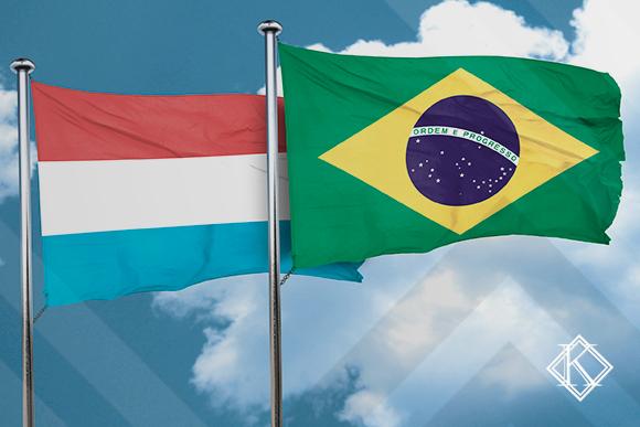"""A imagem mostra as bandeiras do Brasil e de Luxemburgo, ilustrando a publicação """"Acordo de Previdência de Luxemburgo com o Brasil"""", da Koetz Advocacia."""