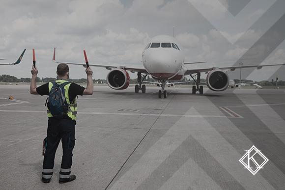 """A imagem mostra um trabalhador aeroviário sinalizando para um avião, e ilustra a publicação """"Aposentadoria Especial do Aeroviário: quis as regras para conquistar?"""", da Koetz Advocacia."""