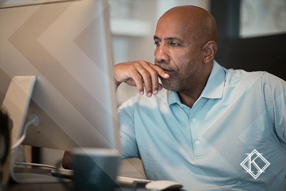 """A imagem mostra um homem sentado lendo no computador. Ilustra a publicação """"Aposentadoria nos EUA para imigrantes: sistema, regras e valores"""", da Koetz Advocacia."""