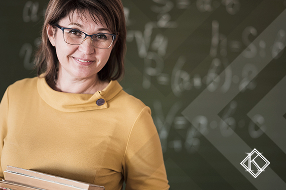 """A imagem mostra uma professora em frente ao quadro verde. Ilustra a publicação """"Previdência para professores: valor e regras da aposentadoria"""", da Koetz Advocacia."""