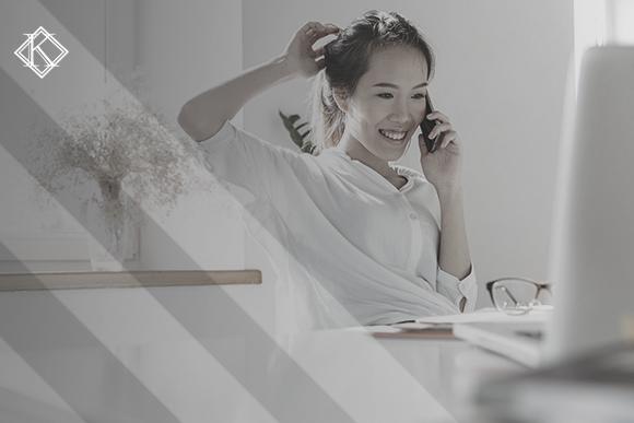 """Mulher sorrindo, falando ao telefone e olhando para a tela do notebook. A imagem ilustra a publicação """"Renovação da Carteira de Registro Nacional Migratório: cuidados importantes"""", da Koetz Advocacia."""