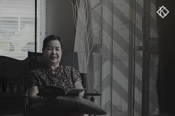 """Imagem de uma senhora asiática sentada em uma cadeira com uma almofada no colo lendo um livro. A imagem tem um filtro cinza de acordo com a identidade visual da Koetz Advocacia. No canto superior direito está a logo branca da Koetz Advocacia. A imagem ilustra o texto """" Vistos brasileiros para estrangeiros """"."""