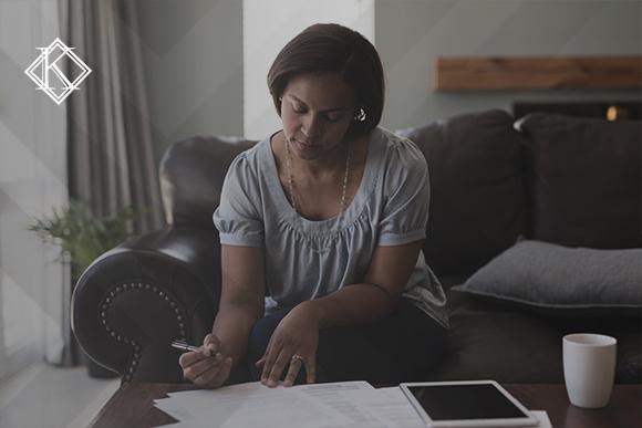 """A imagem mostra uma mulher lendo papéis sobre a mesa. Ilustra a publicação """"Como comprovar atividade de contribuinte individual no INSS?"""", da Koetz Advocacia."""