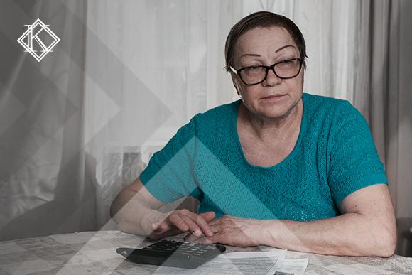 A imagem mostra uma mulher sentada à mesa com papéis e calculadora em sua frente. Ela ilustra a publicação