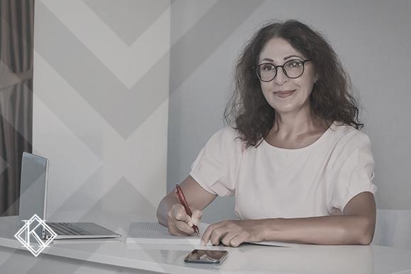 """A imagem mostra uma mulher sentada à mesa de trabalho, sorrindo. Ilustra a publicação """"Como ficou a Previdência com a Reforma?"""", da Koetz Advocacia."""