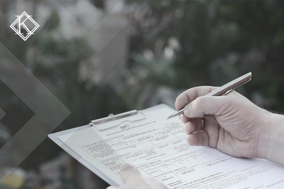 """A imagem mostra uma mão segurando uma caneta sobre uma prancheta com o documento PPP. E ilustra a publicação """"Preenchimento do PPP e aposentadoria especial: como fazer?"""", da Koetz Advocacia."""