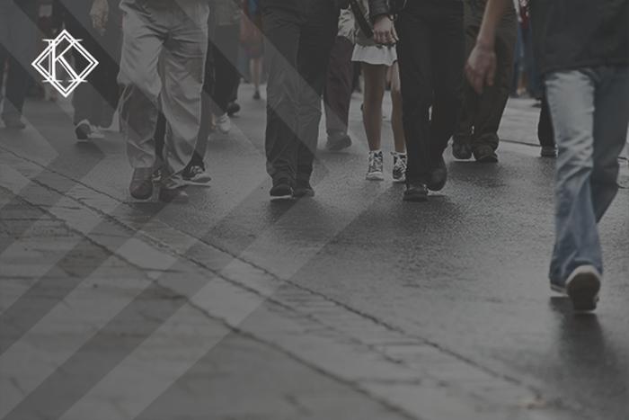 """Imagem de pessoas caminhando na rua. A imagem tem um filtro cinza de acordo com a identidade visual da Koetz Advocacia. No canto superior esquerdo está a logo branca da Koetz Advocacia. A imagem ilustra o texto """"Refúgio no Brasil: o que é necessário para solicitar o visto?"""""""