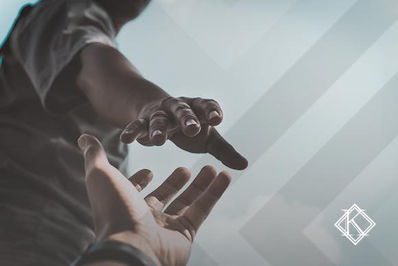 """A imagem mostra uma pessoa vista de baixo estendendo a mão para a câmera a fim de ajudar o observador. A imagem ilustra a publicação """"Serviço de apoio a refugiados no Brasil: quais são e quem é responsável?"""", da Koetz Advocacia."""