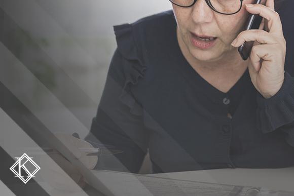 """A imagem mostra uma mulher falando ao telefone e fazendo anotações, e ilustra a publicação """"CTC - tudo sobre a Certidão de Tempo de Contribuição"""", da Koetz Advocacia."""