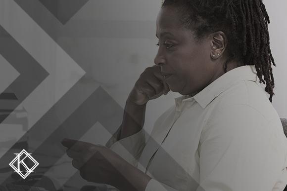 """A imagem mostra uma mulher sentada em sua mesa de trabalho, lendo algo. E ilustra a publicação """"Como faço para saber se a minha aposentadoria foi aprovada?"""", da Koetz Advocacia."""