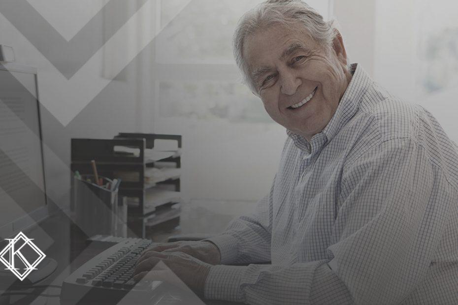 """A imagem mostra um homem usando o computador e sorrindo para a câmera. Ilustra a publicação """"Como saber se posso me aposentar?"""", da Koetz Advocacia."""