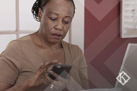 """A imagem mostra uma mulher concentrada, em frente ao computador, usando o celular. Ela ilustra a publicação """"Nova reforma da previdência: entenda o que mudou"""", da Koetz Advocacia."""