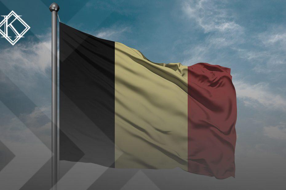 """A imagem mostra uma bandeira da Bélgica, com o céu azul ao fundo. Ilustra a publicação """"A aposentadoria na Bélgica para brasileiro é possível em alguns casos. Neste texto, explicamos quais as opções viáveis e principais regras da previdência belga"""", da Koetz Advocacia."""