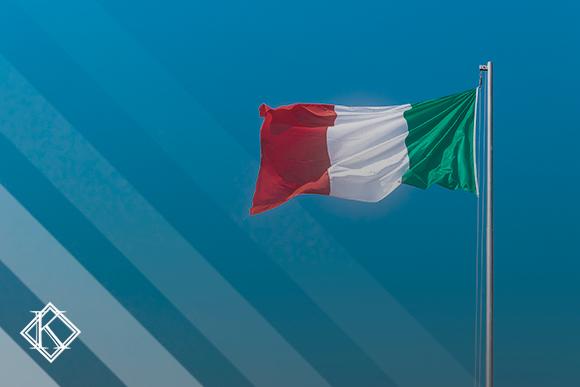 """A imagem mostra a bandeira da Itália balançando, e ilustra a publicação """"Aposentadoria na Itália: regras e valores para estrangeiros."""", da Koetz Advocacia."""