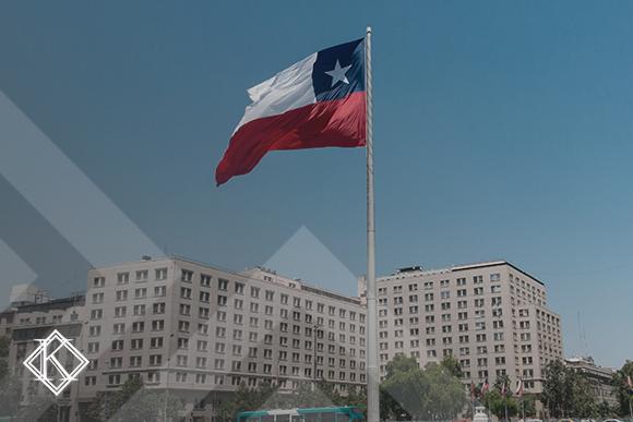 """A imagem mostra uma bandeira do Chile, e ilustra a publicação """"Aposentadoria no Chile: quais as regras para estrangeiros?"""", da Koetz Advocacia."""