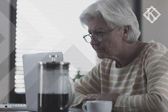 """A imagem mostra uma mulher usando o notebook em uma mesa com uma xícara e uma cafeteira. A imagem ilustra a publicação """"Direito adquirido na aposentadoria do Servidor Público: quem tem?"""", da Koetz Advocacia."""