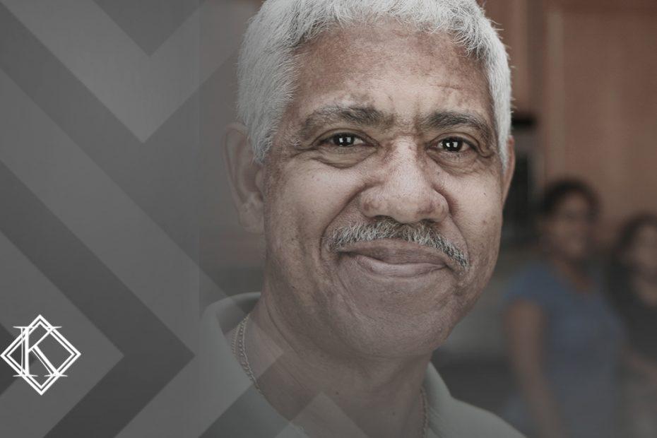 """A imagem mostra um homem sorrindo, com a família desfocada ao fundo, e ilustra a publicação """"Tempo de contribuição para aposentadoria: quanto é necessário?"""", da Koetz Advocacia."""