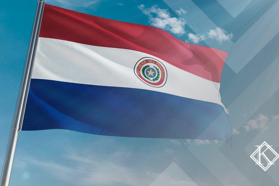 """A imagem mostra uma bandeira do Paraguai com o céu azul no fundo, e ilustra a publicação """"Aposentadoria no Paraguai somando o tempo com o Brasil e mais"""", da Koetz Advocacia."""