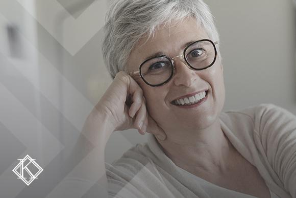 """A imagem mostra uma mulher sorrindo, e ilustra a publicação """"Aposentadoria para professor: quais as regras e os valores vigentes?"""", da Koetz Advocacia."""