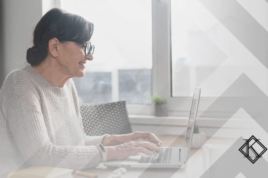 """A imagem mostra uma mulher sorrindo, usando o computador, e ilustra a publicação """"Data certa para requerer aposentadoria: qual você deve seguir?"""", da Koetz Advocacia."""