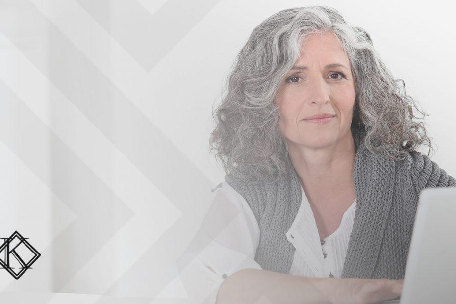 """A imagem mostra uma mulher sorrindo, sentada ao computador. Ilustra a publicação """"Tempo mínimo de contribuição para aposentadoria: como ficou?"""", da Koetz Advocacia."""