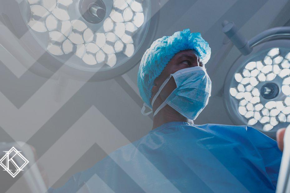"""A imagem mostra um cirurgião visto de baixo, em uma mesa de cirurgia, e ilustra a publicação """"Aposentadoria Especial do Cirurgião: regras, valor e provas"""", da Koetz Advocacia."""