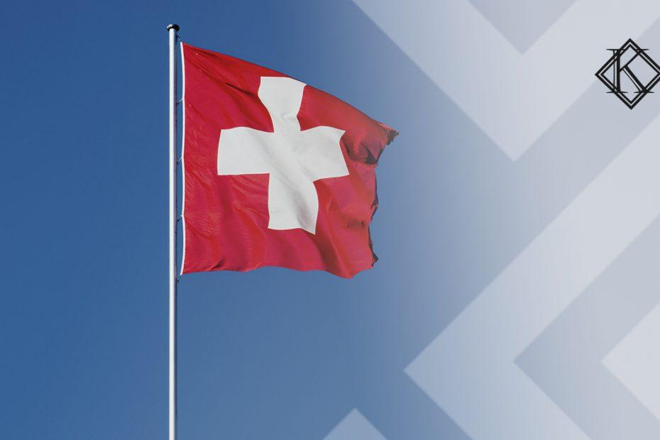"""A imagem mostra a bandeira da Suíça, ilustrando a publicação """"Aposentadoria na Suíça: quais são as regras para os estrangeiros?"""", da Koetz Advocacia."""