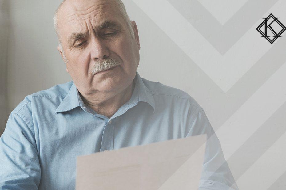 """A imagem mostra um homem lendo um documento, e ilustra a publicação """"Como ficou a reforma da previdência para aposentadoria a partir de 2021?"""", da Koetz Advocacia."""