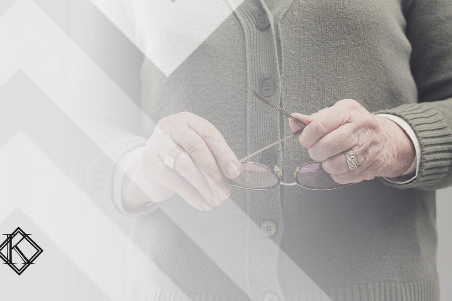 """A imagem mostra as mãos de uma pessoa mais velha limpando um óculos, e ilustra a publicação """"Pensão por morte do servidor Estadual e Municipal, como ficou?"""", da Koetz Advocacia."""