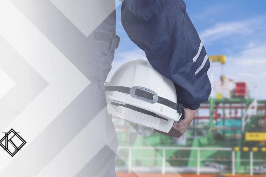 """A imagem mostra um capacete sendo segurado sob o braço de um homem de costas, com uma plataforma petrolífera ao fundo. A imagem ilustra a publicação """"Aposentadoria Especial na Engenharia de Petróleo e Gás"""", da Koetz Advocacia."""