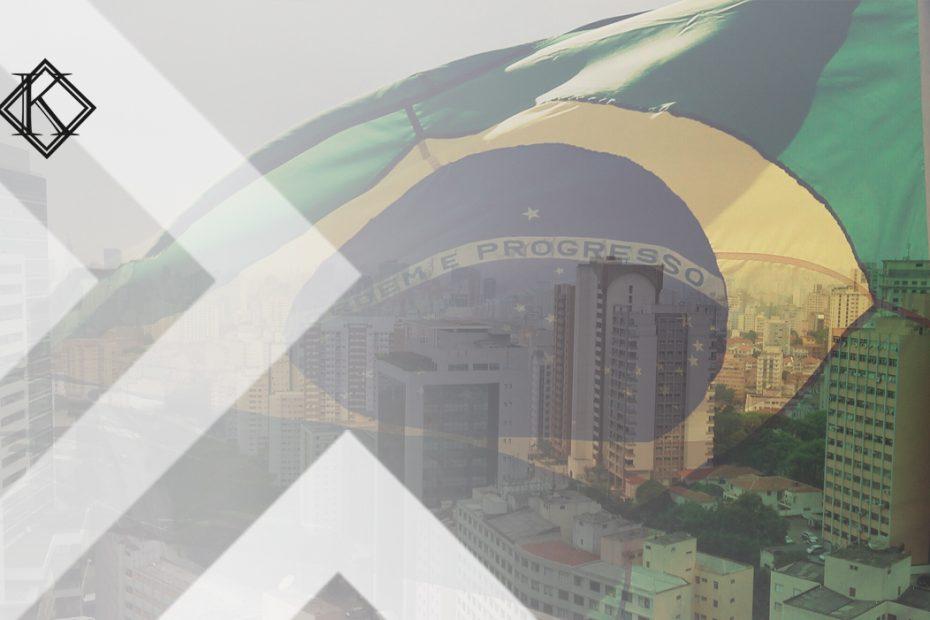 """A imagem mostra uma bandeira do Brasil sobreposta a uma imagem de uma cidade brasileira, e ilustra a publicação """"Embaixadas e Consulados no Brasil: lista de endereços e contatos"""", da Koetz Advocacia."""