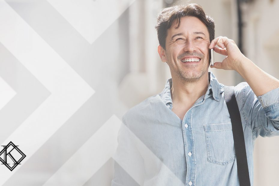 """A imagem mostra um homem sorrindo e caminhando na rua enquanto atende o telefone, e ilustra a publicação """"Imigrante que comprar imóvel pode ter autorização de residência brasileira"""", da Koetz Advocacia."""