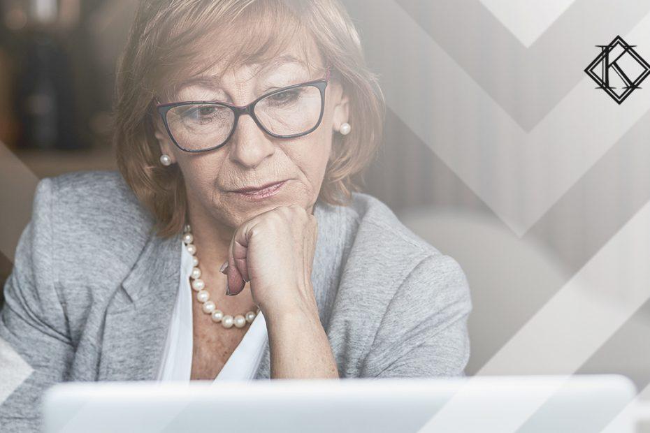 """A imagem mostra uma mulher lendo algo no computador, e ilustra a publicação """"Imposto na Aposentadoria nos EUA cobrado indevidamente pelo Brasil"""", da Koetz Advocacia."""