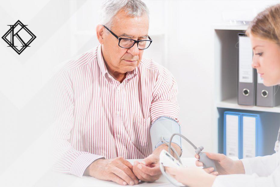 """A imagem mostra uma enfermeira medindo a pressão de um homem, ilustrando a publicação """"Licença para tratamento de saúde do servidor público: quais as regras?"""", da Koetz Advocacia."""