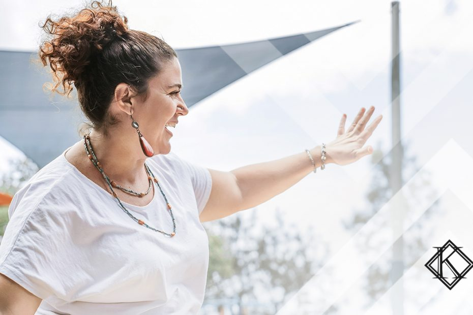 """A fotografia mostra uma mulher sorrindo e acenando em um ambiente externo, e ilustra a publicação """"Brasileiro Naturalizado: como conseguir a naturalização brasileira?"""", da Koetz Advocacia."""