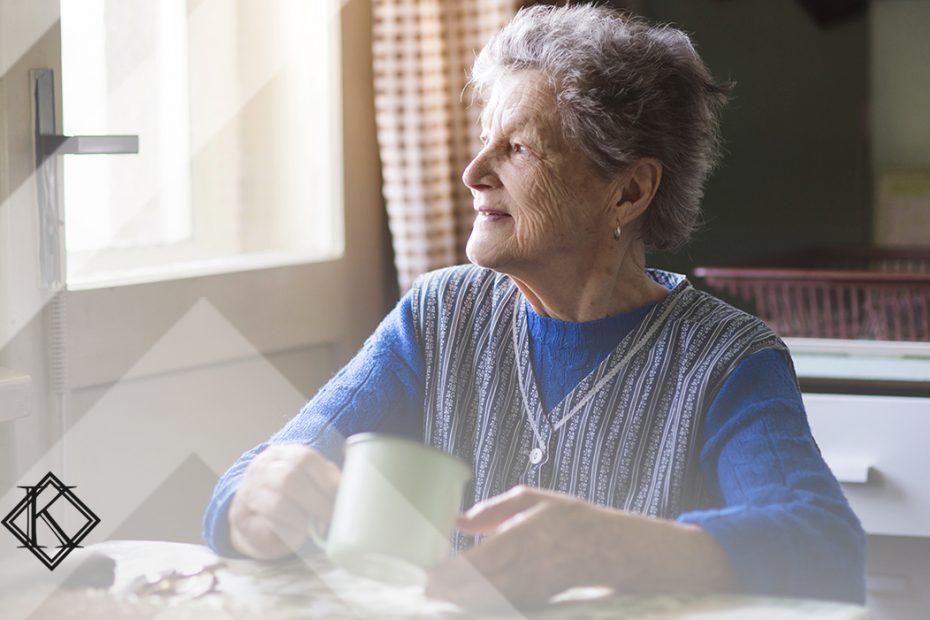 """A imagem mostra uma mulher sentada na mesa olhando para fora da janela, e ilustra a publicação """"Concessão simultânea de pensão a companheira e cônjuge é possível?"""", da Koetz Advocacia."""