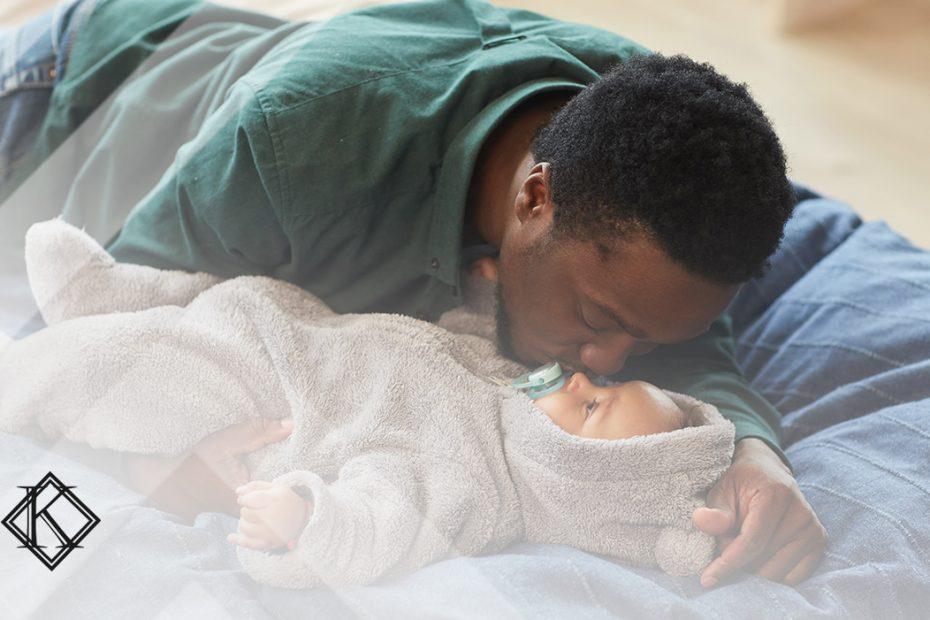"""A imagem mostra um homem beijando um bebê na testa, e ilustra a publicação """"Visto permanente por reunião familiar no Brasil, como obter?"""", da Koetz Advocacia."""